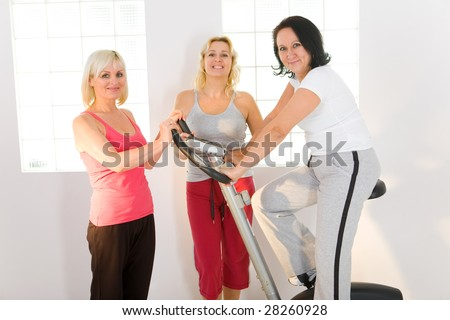 Three women dressed sportswear. One of them exercising on bike. - stock photo