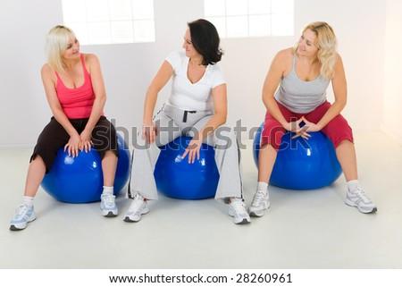 Three women dresset sportswear sitting on fitness ball and talking. - stock photo