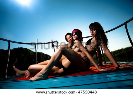 Three women enjoying  summer on a boat and posing under the sun. - stock photo