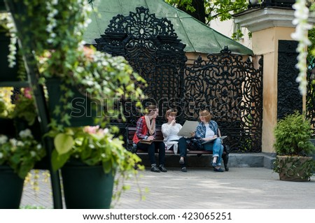 three women friends sitting on the bench Sokolniki Park, Russia - May 7, 2016: three women friends sitting on a bench in the park and maybe draw something very passionate about their occupation - stock photo