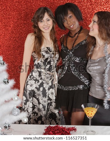 Three women friends smiling at a christmas party, having fun with a white decorated tree in a red glitter background. - stock photo
