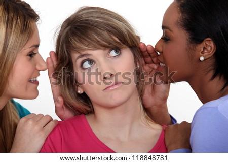 Three women gossiping. - stock photo
