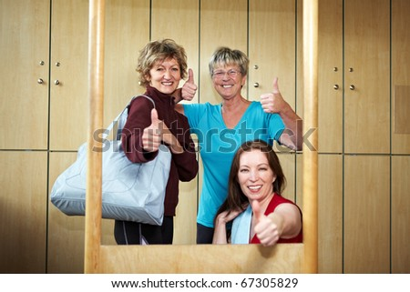 Three women holding their thumbs up in locker room - stock photo