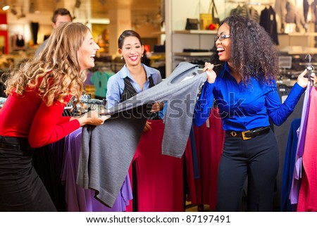 Three women in a shopping mall downtown looking for clothes - stock photo