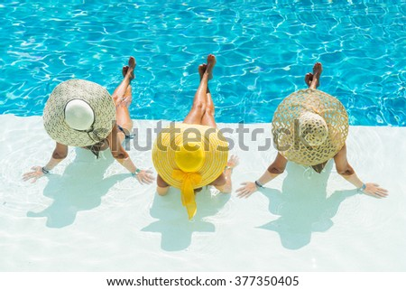 Three women in bikini wearing a straw hat by the swimming pool - stock photo