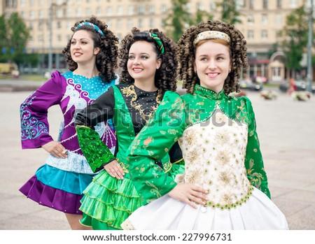 Three women in irish dance dresses and wig posing  - stock photo