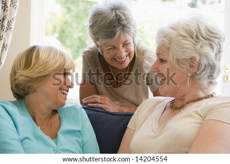 Three women in living room talking and smiling - stock photo