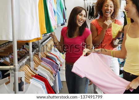 Three women in shop selecting clothes - stock photo