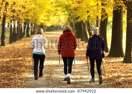Three women in the park - Nordic walk - stock photo