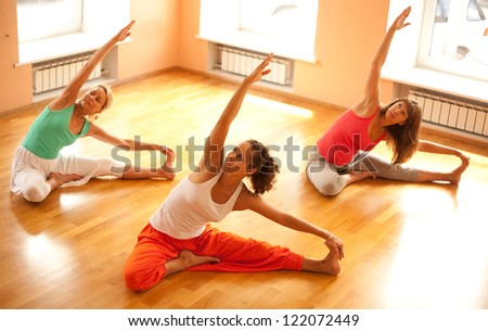 Three women is doing yoga at health club - stock photo