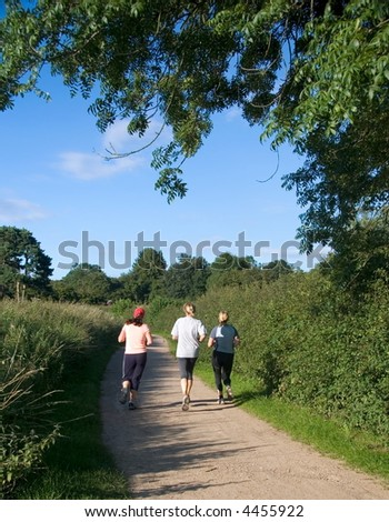 three women jogging in countryside