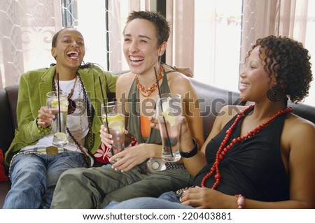 Three women laughing and drinking on sofa - stock photo
