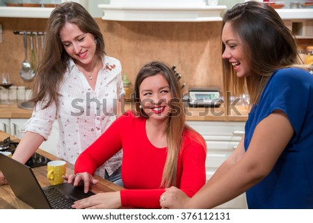 Three women laughing and surfing the net on computer at home. Girls at home shopping online with laptop and having fun.