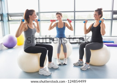 Three women lifting weights on exercise balls in gym - stock photo
