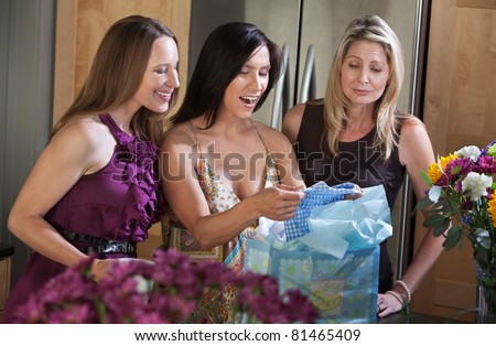 Three women look at gifts at a baby shower