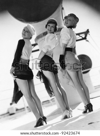 Three women looking over their shoulders and showing their legs - stock photo