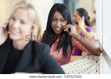 Three women of varying ethnicities sitting on a couch, talking on their cell phones, while smiling. - stock photo