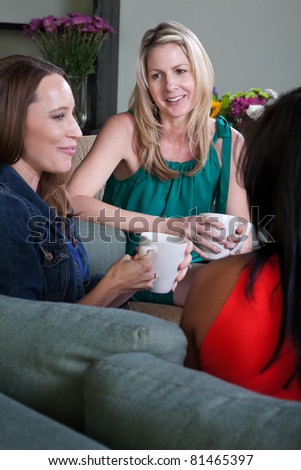 Three women on a sofa talk and drink coffee