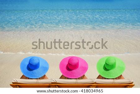 Three women on beach in bright hats traveling - stock photo