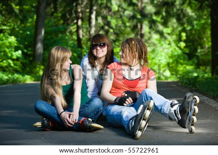 Three women on rollerblades at park - stock photo