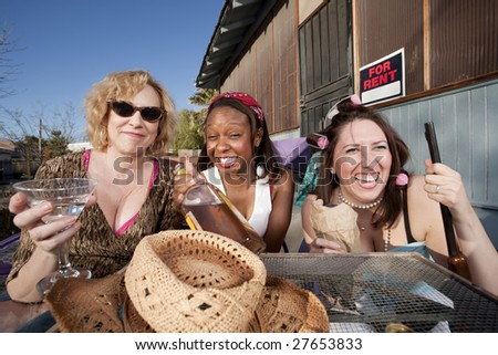 Three women outside a house drinking alcoholic beverages - stock photo