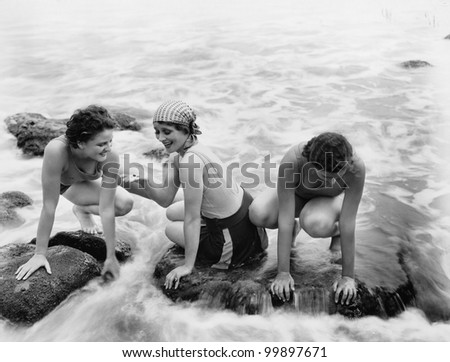 Three women playing in water on the beach - stock photo