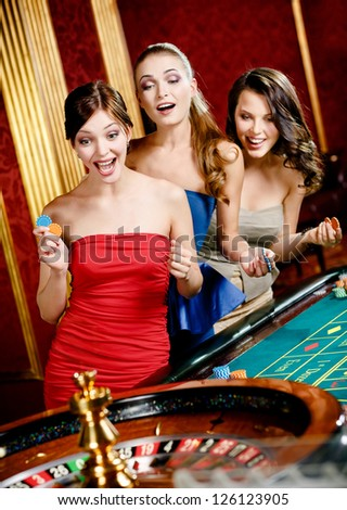 Three women playing roulette at the casino - stock photo