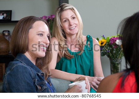 Three women sit together in a room - stock photo