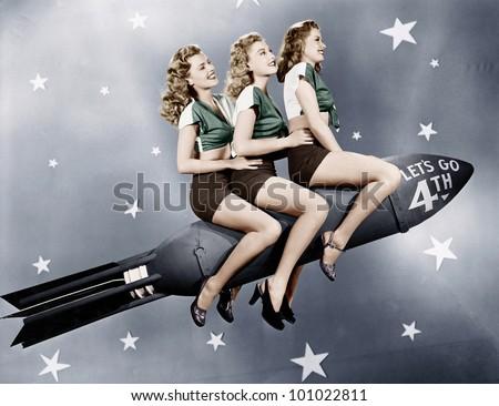Three women sitting on a rocket - stock photo