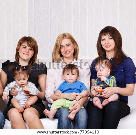 Three women sitting with babies on the sofa - stock photo