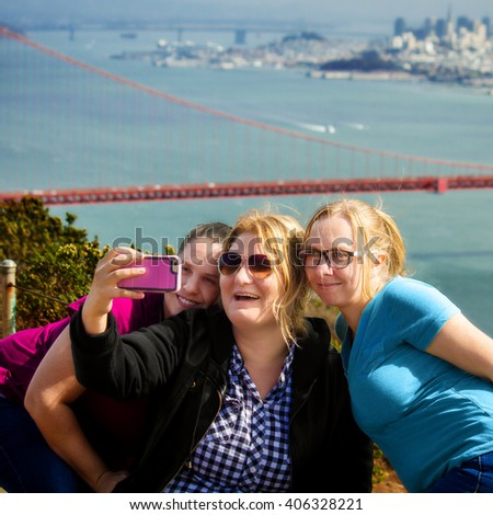 Three women take a selfie at the Golden Gate bridge on their road trip. - stock photo
