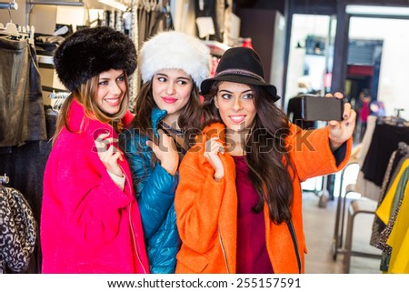 Three women taking a selfie wearing colorful coats in a clothing store. They are happy and enjoy funny clothes. Shopping concept, also related to social media addiction. - stock photo