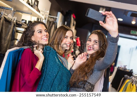 Three women taking a selfie while shopping in a clothing store. They are happy and smiling at camera. Shopping concept, also related to social media addiction. - stock photo