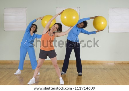 Three women using exercise balls in fitness class - stock photo