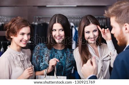 Three wonderful women flirt with salesperson - stock photo