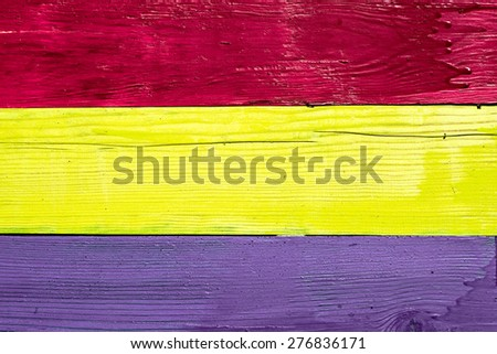 Three wooden boards painted burgundy, yellow and purple paint