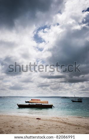 Three wooden boats used to transport tourists from Stone Town to Prison Island - a popular tourist attraction famous for its prison and giant Tortoises. - stock photo