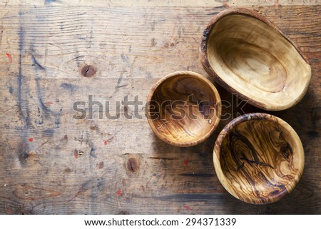 Three wooden bowls from olive tree on a wooden background. background for restaurants - stock photo
