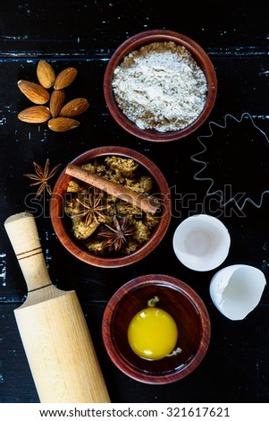 Three wooden bowls with ingredients for baking cake (flour, egg, brown sugar) on dark vintage background. Top view. - stock photo