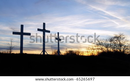 Three wooden crosses sit upon a hill in the sunset