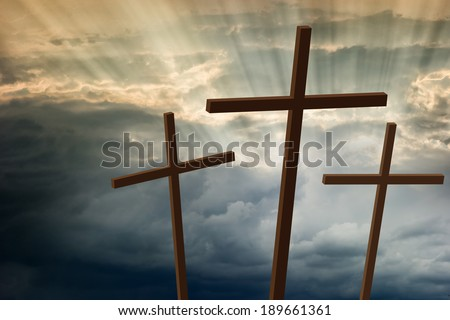 Three wooden crosses stand against a dramatic evening sky with radiant beams penetrating clouds
