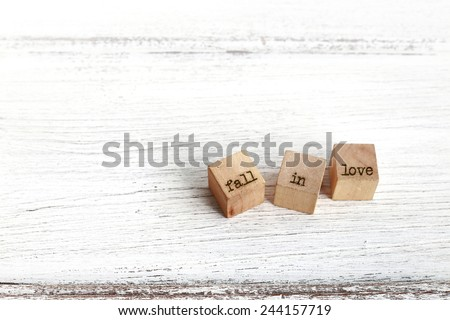 "Three wooden cubes with ""fall in love "" words on white wood, background for valentine's day. - stock photo"