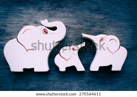 Three wooden elephants, traditional toys, symbol of happy strong family, filtered photo. - stock photo