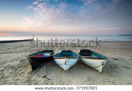 Three wooden fishing boats on the beach at Durley Chine in Bournmouth, Dorset - stock photo