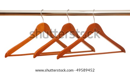 Three wooden hangers on a stainless steel clothes rail isolated on white