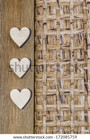 three wooden hearts on wooden and woven background - stock photo