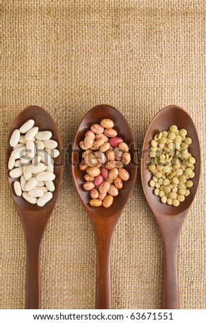 Three wooden spoon on burlap with beans and lentil. - stock photo
