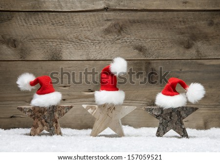 Three wooden stars with santa hats on wooden background - handmade idea for a greeting card - stock photo