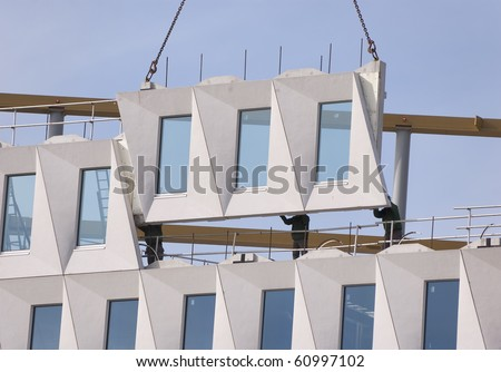 Three workers positioning a hoisted facade element - stock photo