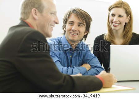 Three workers sit and talk at a desk - stock photo